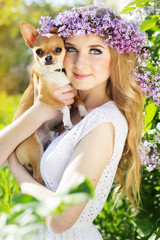 Beautiful girl with lilac flowers is holding chuhuahua dog
