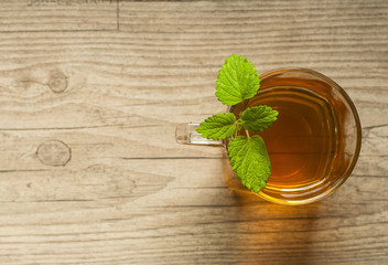 cup of tea with mint on wooden table