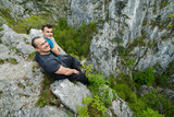 Father and son sitting on the edge of a cliff