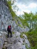Hiker man walking to a mountain rocky trail