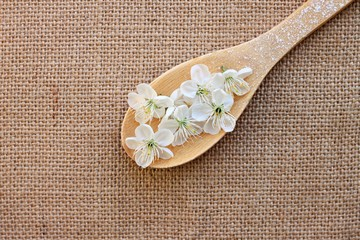 kitchen wooden spoon with blossom jute cloth background