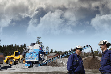 industry workers and large stone quarry plant, trucks in action