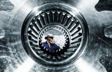 engineer, mechanic, seen through a giant cogwheels axle