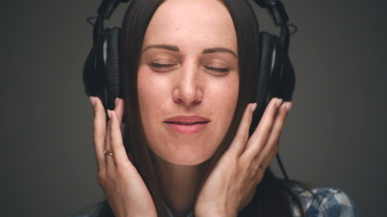 Woman listening music in headphones on grey background