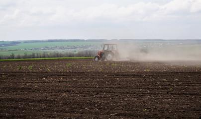 Украина, вспаханное поле и трактор в клубах пыли