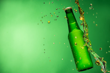 Bottle of beer with splash, on green background