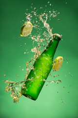 Bottle of fruit beer with splash, on gree