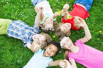 Kinder auf der Wiese Hände halten