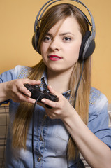 Closeup young girl playing video games with headphones on