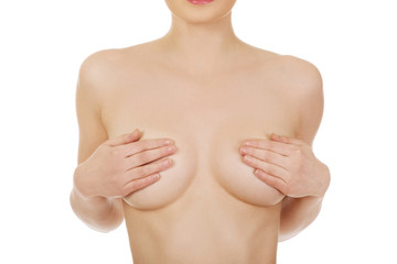 Topless woman covers her breast.