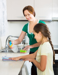 girl and mom tidy kitchen