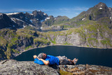 Man takes rest on top of mountain in Norway