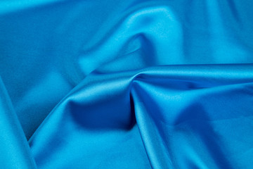 Texture of blue silk cloth with waves.