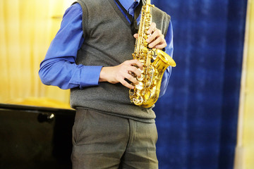 The performer plays a saxophone during a concert