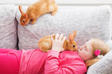 girl with two rabbits indoor