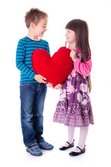 Girl and boy holding a big red heart shaped pillow