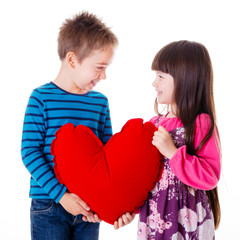 Portrait of girl and boy holding a big red heart shaped pillow