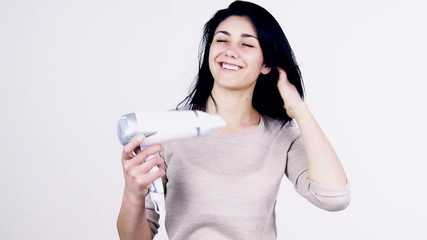 Cute girl blow drying hair in studio smiling medium shot