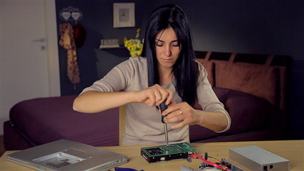 Cute woman repairing hard disk at home