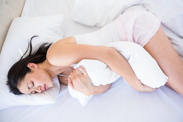 Pretty brunette with stomach pain on bed
