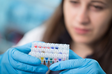 Young woman with PCR tubes in genetic laboratory