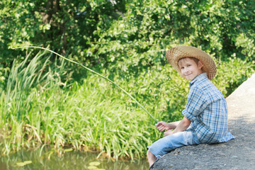 Angling boy with wooden rustic fishing rod