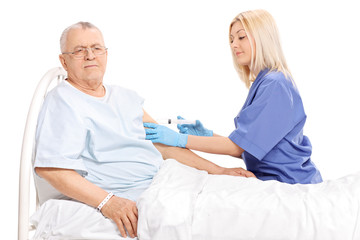 Female doctor giving an injection to a mature patient