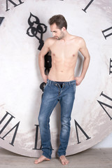 A shirtless young man is standing in front of a clock