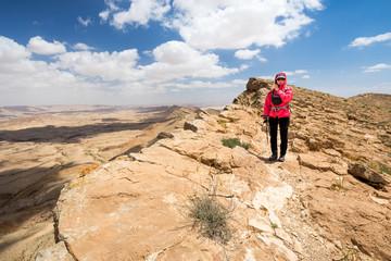 Woman standing desert mountain edge.