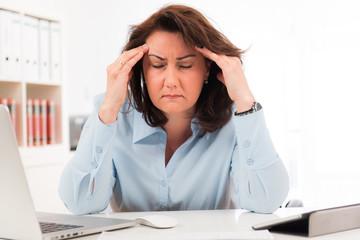 businessfrau hat kopfschmerzen am arbeitsplatz