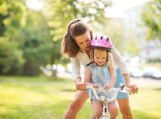 Mother shows daughter how to ride a bike holding handlebars