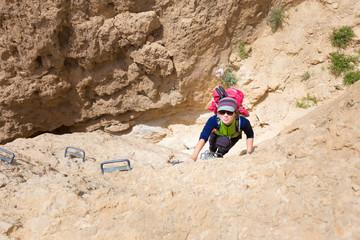 Young woman climbing desert canyon cliff.