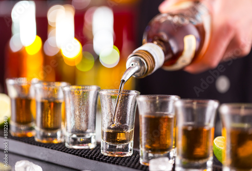 Fotografiet Barman pouring hard spirit into glasses