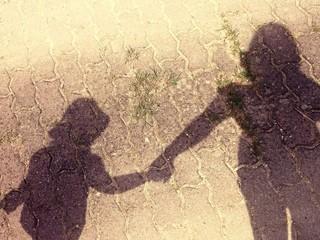 Schatten von Mutter und Tochter die sich an der Hand halten
