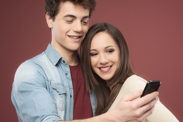 Young teen couple with smartphone