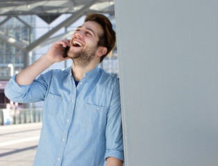 Young man talking on mobile phone and laughing