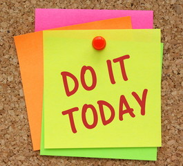 Do It Today reminder note on a cork notice board