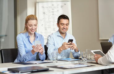 smiling business people with smartphones in office