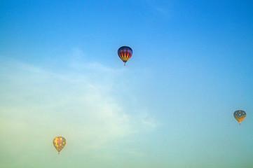 three hot air balloons flying above morning fog