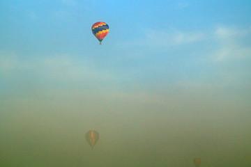 three hot air balloons flying through morning fog