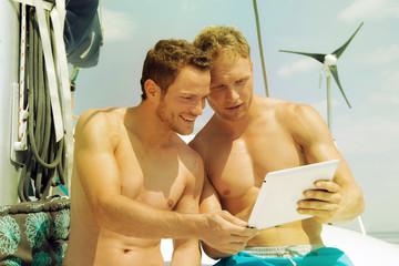 Zwei Männer auf einem Segelboot schauen auf einen Tablet PC