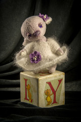 Doll hare in a lilac dress on the cube.
