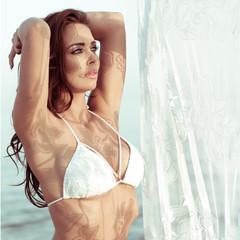 Woman in White Bikini Standing Near Lace Curtain
