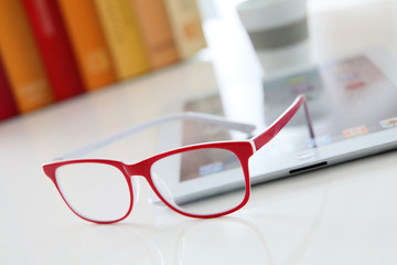 Red eyeglasses set on table by digital tablet