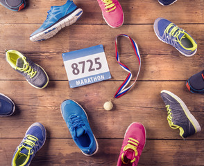 Running shoes, number and gold medal on a wooden background