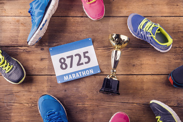 Running shoes, number and gold cup on a wooden background