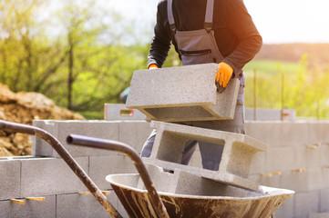 Unrecognizable bricklayer building a wall loading a wheelbarrow