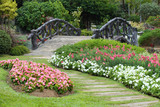 Fototapety landscape of floral gardening with pathway and bridge in garden