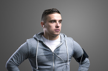 Handsome young runner. Studio shot on gray background.
