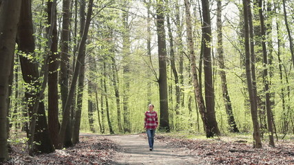 Young woman walking on a forest path with arms outstretched